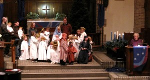 Angels, shepherds and wise people gather around Mary, Joseph, and Jesus while the Christmas story is read.